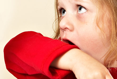 Photo of little girl coughing into sleeve